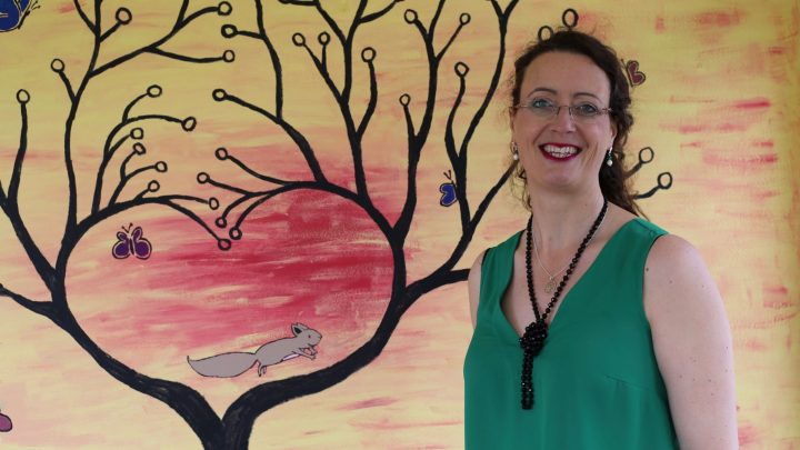 Kate beside her full-size tree-of-life mural at home